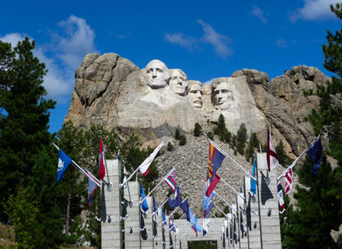 View of presidents at Mount Rushmore with state flags in foreground